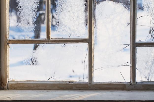 Vecchia finestra di legno con gelo invernale