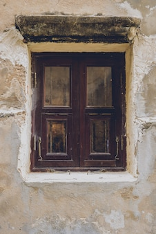 Vecchia finestra di legno tradizionale d'annata e parete del cemento