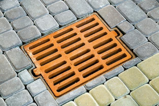 Vecchia grondaia arrugginita del metallo per acqua piovana sul marciapiede pavimentato pietra