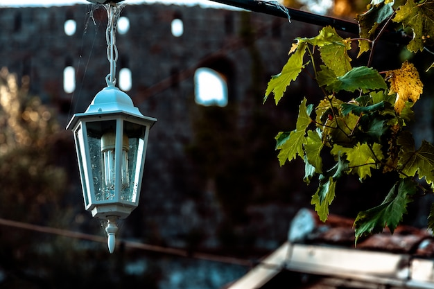 Vecchia lampada d'annata nera sul muro di mattoni con le candele decorative dentro alla vecchia casa di città