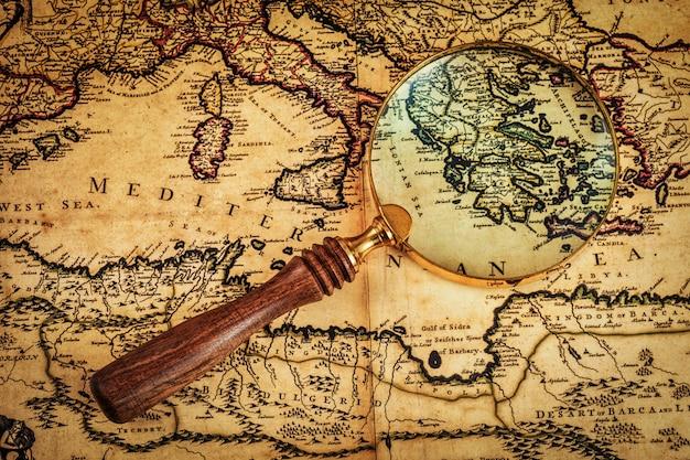 Vecchia lente d'ingrandimento d'annata sulla mappa antica