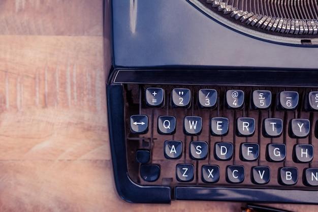 Vecchia macchina da scrivere sullo scrittorio di legno sull'ufficio creativo