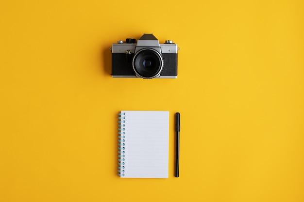 Vecchia macchina fotografica analogica d'annata accanto ad un blocco note a spirale pronto