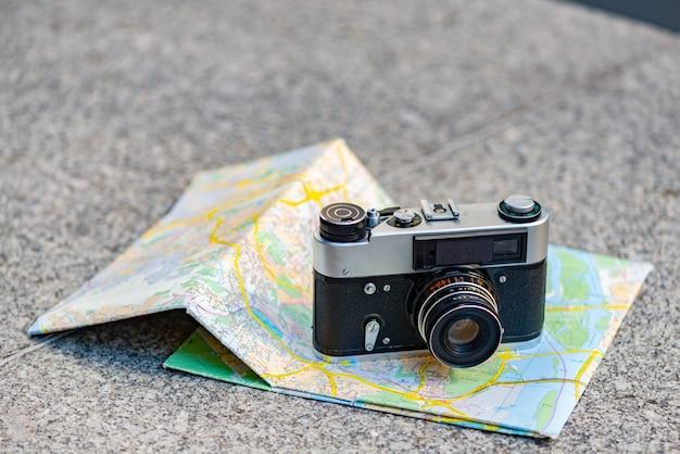 Vecchia macchina fotografica d'annata su un fondo di vecchia mappa che si trova sulla pietra