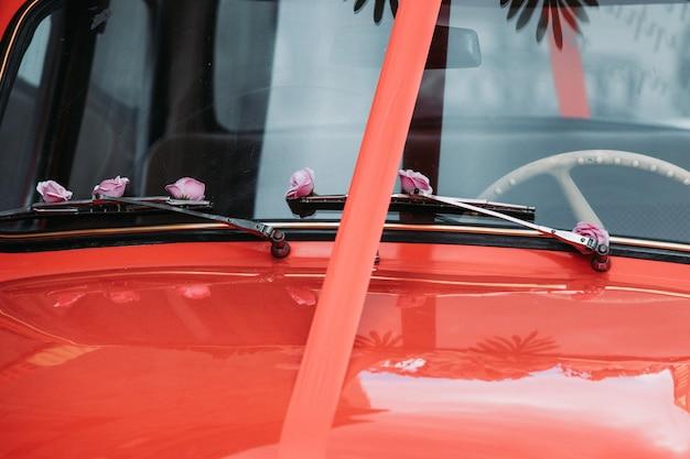 Vecchia macchina rossa con un nastro