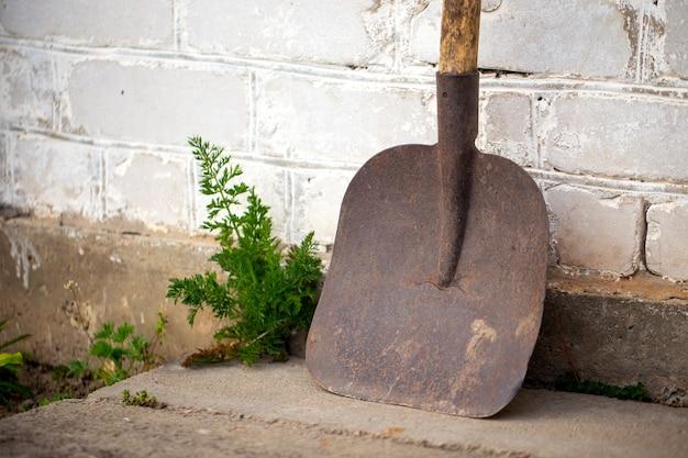 Vecchia pala sporca usata appoggiata al muro di mattoni bianchi