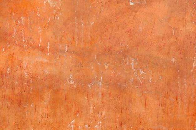 Vecchia parete arancio astratta del cemento con struttura e fondo della crepa