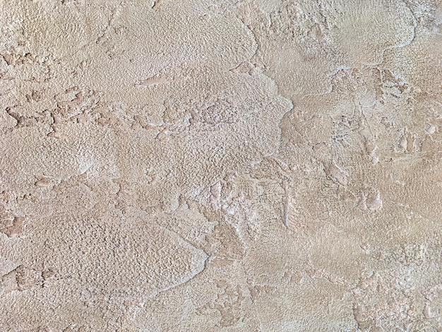 Vecchia parete beige coperta di intonaco irregolare