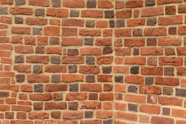 Vecchia parete della fortezza del mattone rosso con il textute grigio del mortaio del cemento