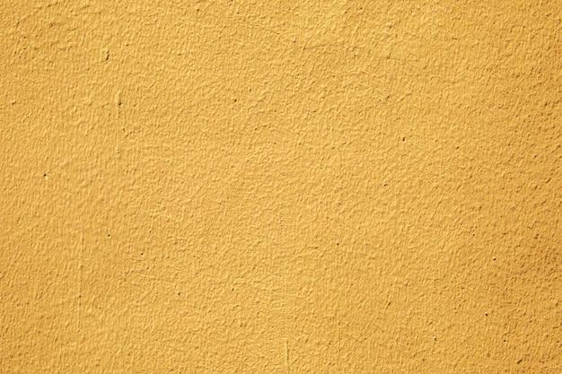 Vecchia parete gialla del cemento per strutturato e.