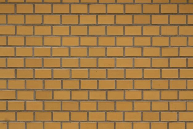 Vecchia parete gialla della fortezza del mattone con il textute grigio del mortaio del cemento