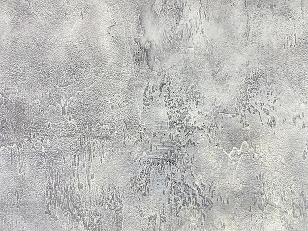 Vecchia parete grigia coperta di gesso irregolare, struttura della superficie di pietra d'argento misera d'annata