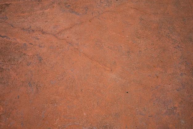 Vecchia parete incrinata o struttura e fondo del pavimento del cemento arancio