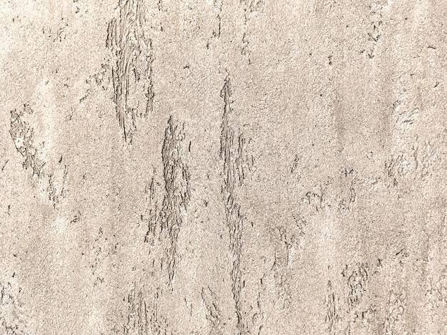 Vecchia parete marrone chiaro coperta di intonaco irregolare malandato. struttura della superficie d'annata della pietra bronzea, primo piano