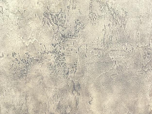 Vecchia parete marrone chiaro coperta di intonaco irregolare malandato