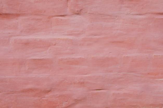 Vecchia parete rosa con cemento e mattone danneggiati miseri del gesso