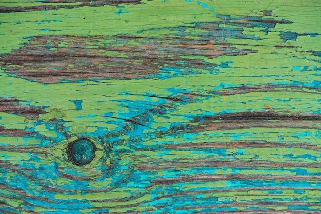 Vecchia parete rustica dipinta di legno con la tintura a fiocchi verde blu.