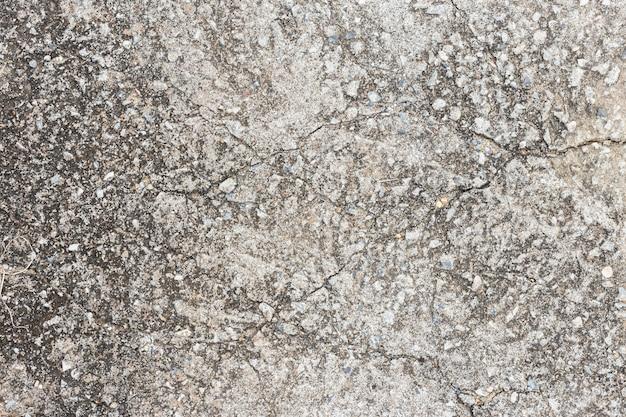 Vecchia parete scura sporca astratta del cemento su struttura a terra.
