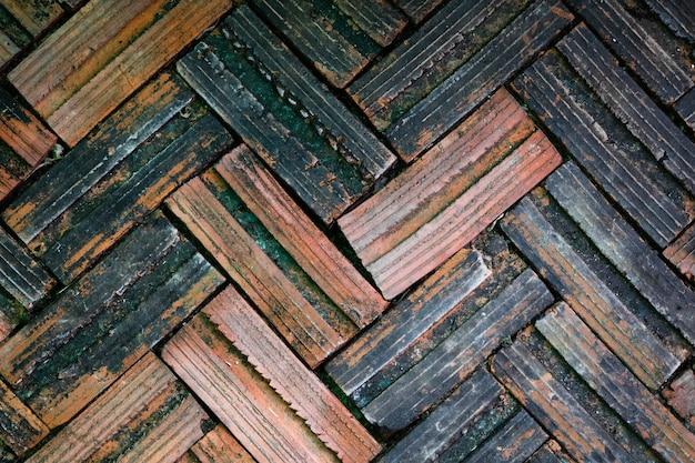 Vecchia pavimentazione in mattoni su uno sfondo di marciapiede