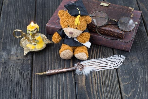 Vecchia penna stilografica, candela in un candeliere, bicchieri, libri e un orso laureato in un cappello laureato