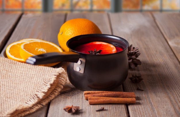 Vecchia pentola del metallo di vin brulé saporito con il vaso con le spezie e i frutti arancio sulla tavola di legno