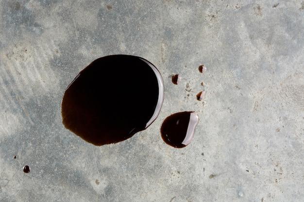 Vecchia perdita di olio motore nero olio o gocciolare sul pavimento di cemento in vista dall'alto
