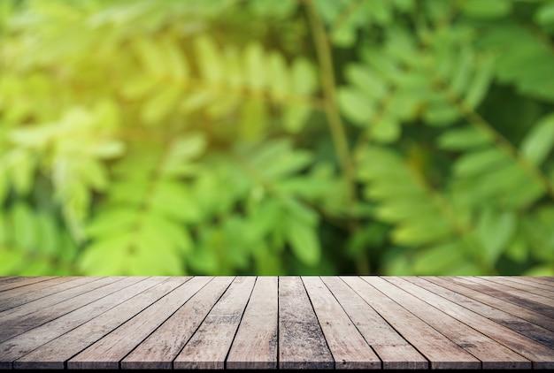 Vecchia plancia di legno con il fondo naturale astratto delle foglie verdi per l'esposizione del prodotto