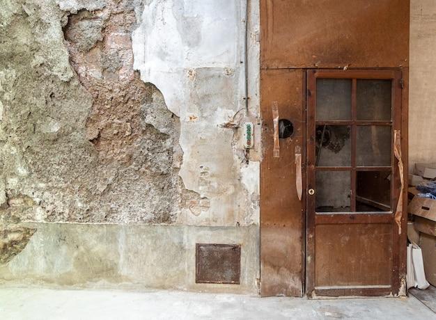 Vecchia porta del carrello elevatore su una parete rotta