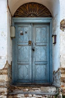 Vecchia porta di legno blu nell'edificio opsharpanny