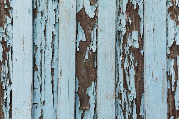 Vecchia porta di legno con peeling e vernice bianca incrinata.