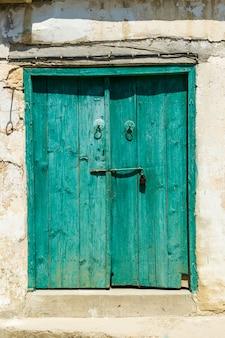 Vecchia porta di legno dipinta con vernice bianca