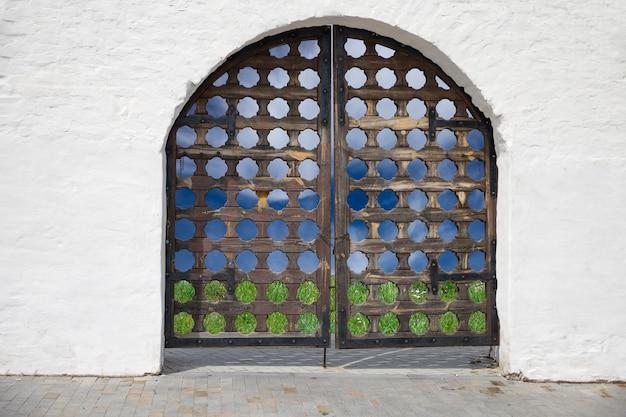 Vecchia porta scolpita nel muro bianco