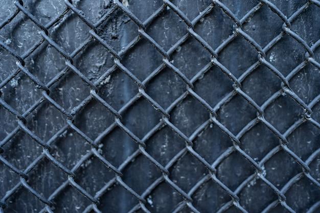 Vecchia priorità bassa nera del metallo ricoperta di griglia della rete metallica. struttura in metallo