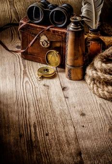Vecchia retro bussola d'annata, binocolo e cannocchiale sulla tavola di legno.
