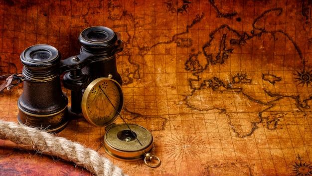 Vecchia retro bussola e cannocchiale d'annata sulla mappa di mondo antica