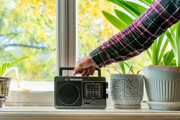 Vecchia retro radio con l'antenna sulla finestra a casa che gioca musica f