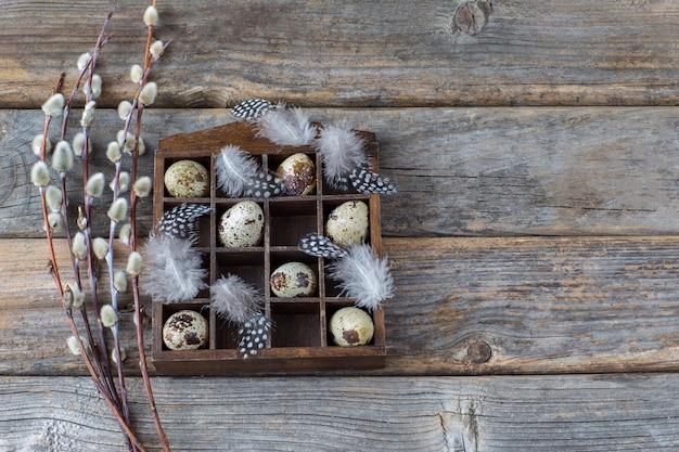 Vecchia scatola con uova di quaglia, piume e salice su fondo in legno - sfondo pasqua