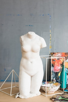 Vecchia statua femminile rotta bianca e attrezzature di verniciatura