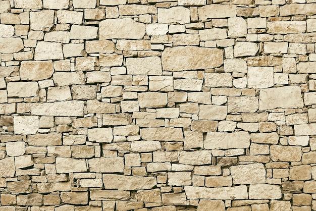 Vecchia struttura beige del fondo della parete di pietra