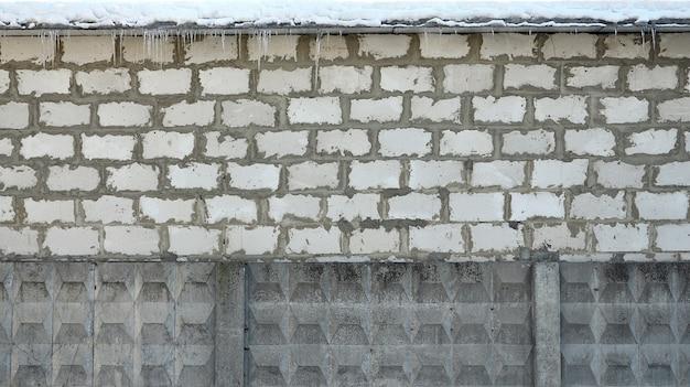 Vecchia struttura bianca stagionata del muro di mattoni