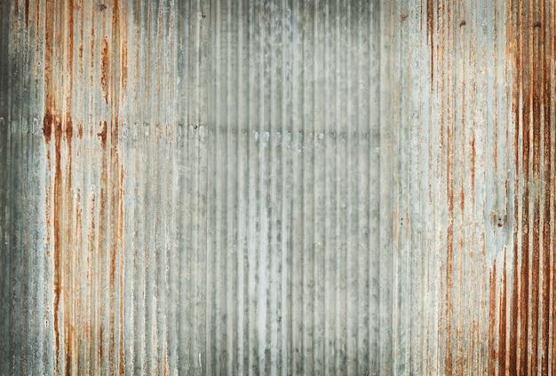 Vecchia struttura della parete dello zinco, arrugginita sul rivestimento metallico galvanizzato del pannello.