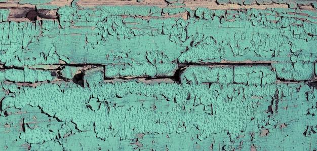 Vecchia struttura di legno. tavola di legno stagionata, vernice color menta e crepe.