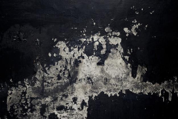 Vecchia struttura nera della pittura che si sbuccia fuori dal fondo del muro di cemento
