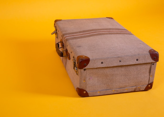 Vecchia valigia su uno sfondo giallo, concetto di viaggio