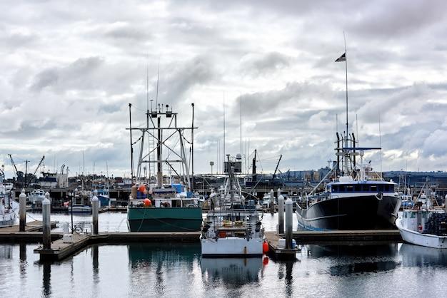 Vecchie barche in un porto e un molo di sera