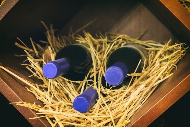 Vecchie bottiglie di vino in scatola di legno con paglia