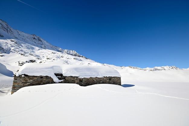 Vecchie capanne del pascolo nel fondo scenico di inverno, inverno nelle alpi