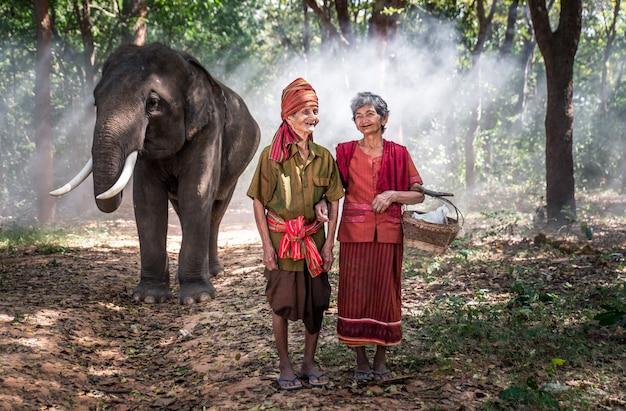 Vecchie coppie che camminano con il loro elefante nella giungla, in tailandia