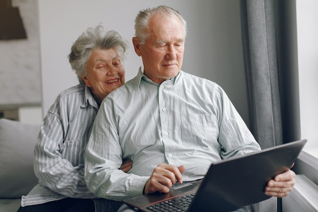 Vecchie coppie eleganti che si siedono a casa e che per mezzo di un computer portatile
