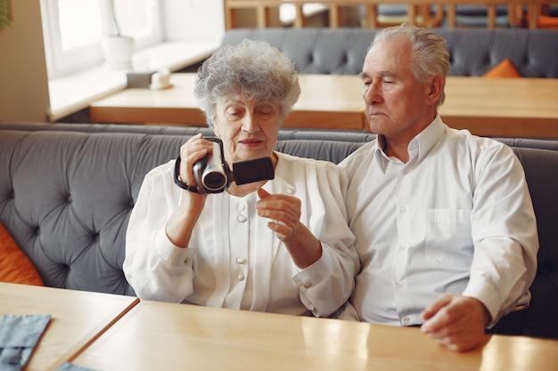 Vecchie coppie eleganti in un caffè facendo uso di una macchina fotografica